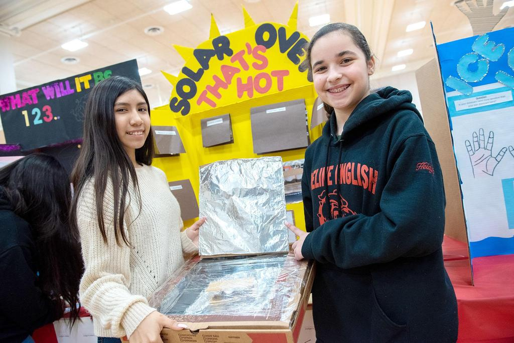 Two students hold their creation, a solar oven that's hot