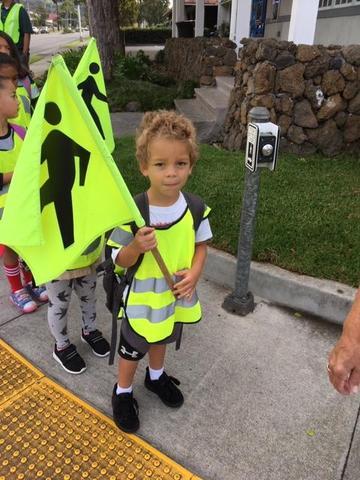 child holding a crosswalk flag