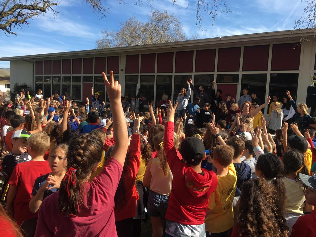 students at an assembly holding up fingers to indicate quiet sign