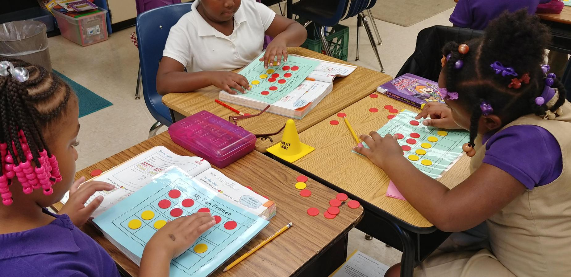 Students using manipulatives to complete math problems.