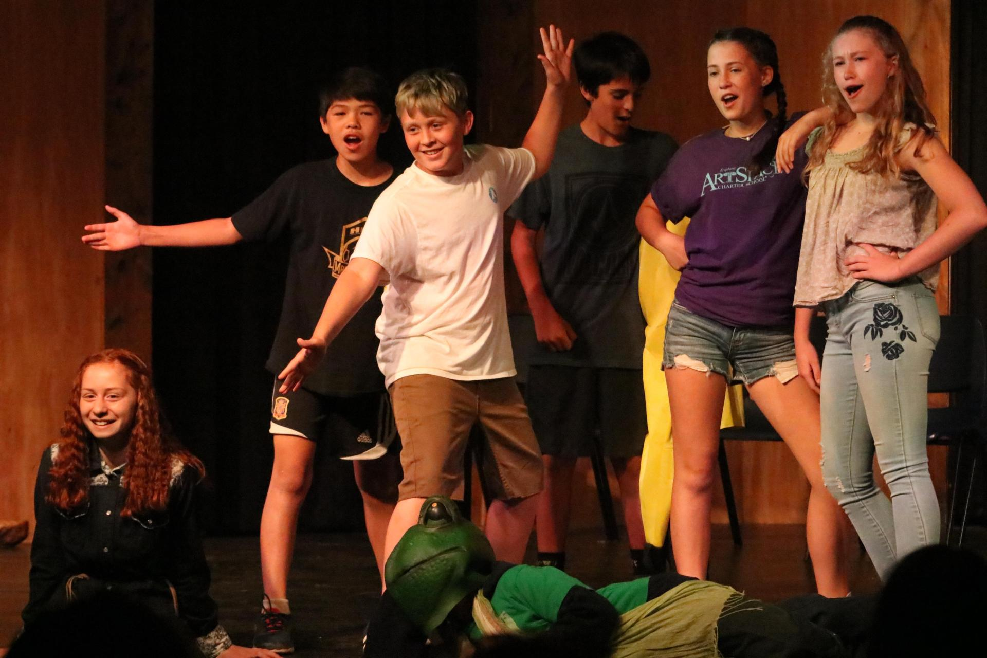 Middle schoolers pose, smiling, on the theater stage.