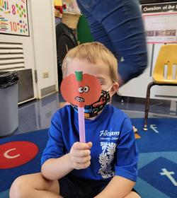 Child with pumpkin drawing on stick in front of face