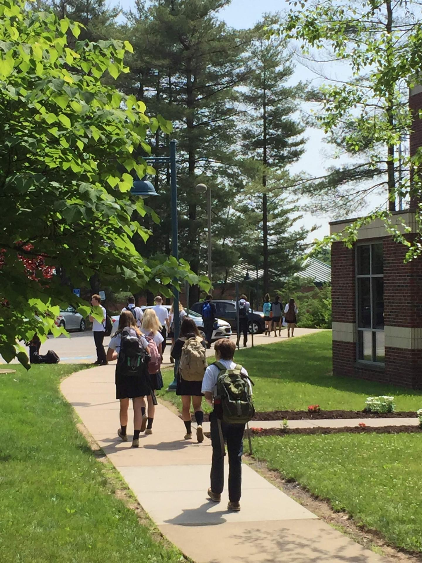 Students leaving campus on a sunny spring day