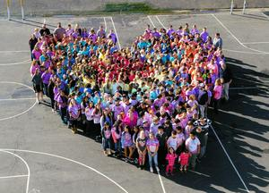aerial shot of 100s of kids in multicolored t shirts forming a heart