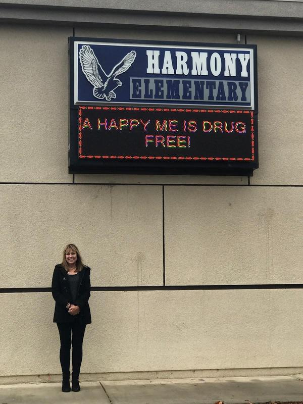 Kristine Krasovec standing in front of a Harmony sign