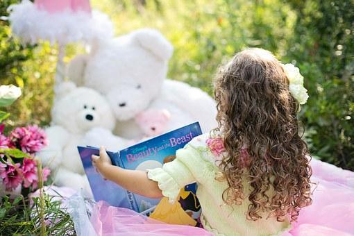 girl reading a book to stuffed animals