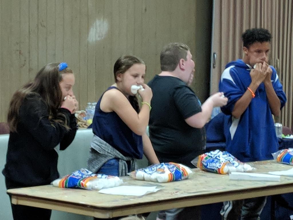 Students eating marshmallows for a competition