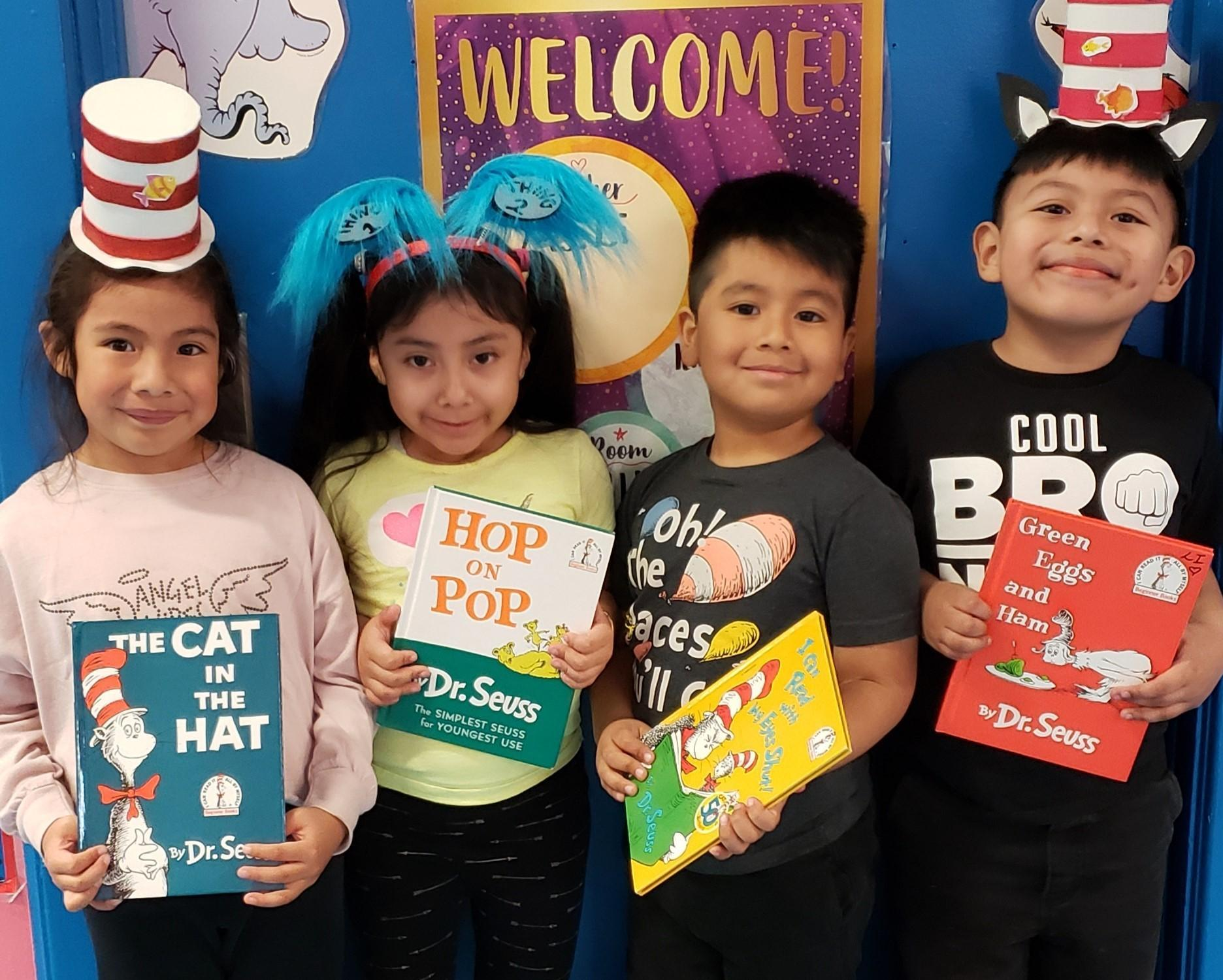 Kindergarten students wearing 'Seusical' headbands and holding books by Dr. Seuss.