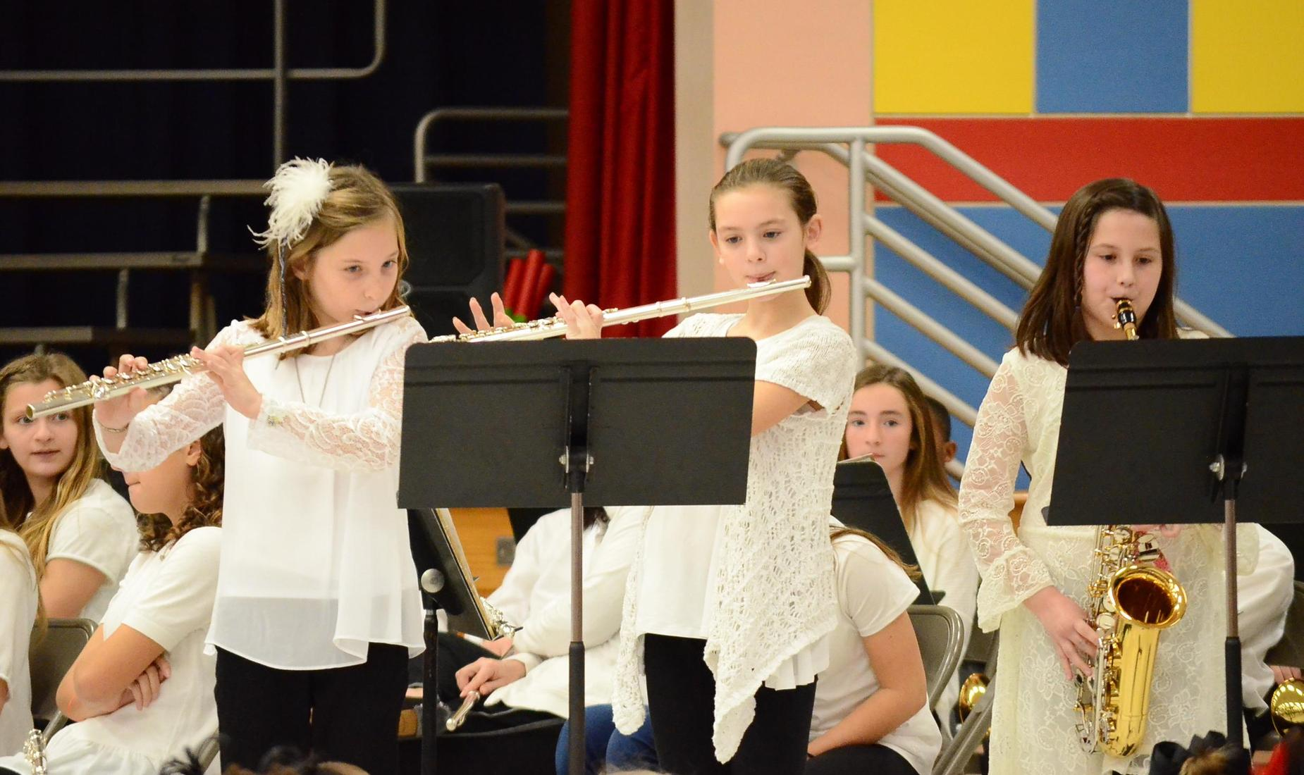 Trio of 3 girls dress in white blouses and black pant performing at their winter/holiday concert. 2 flutists and 1 saxophone