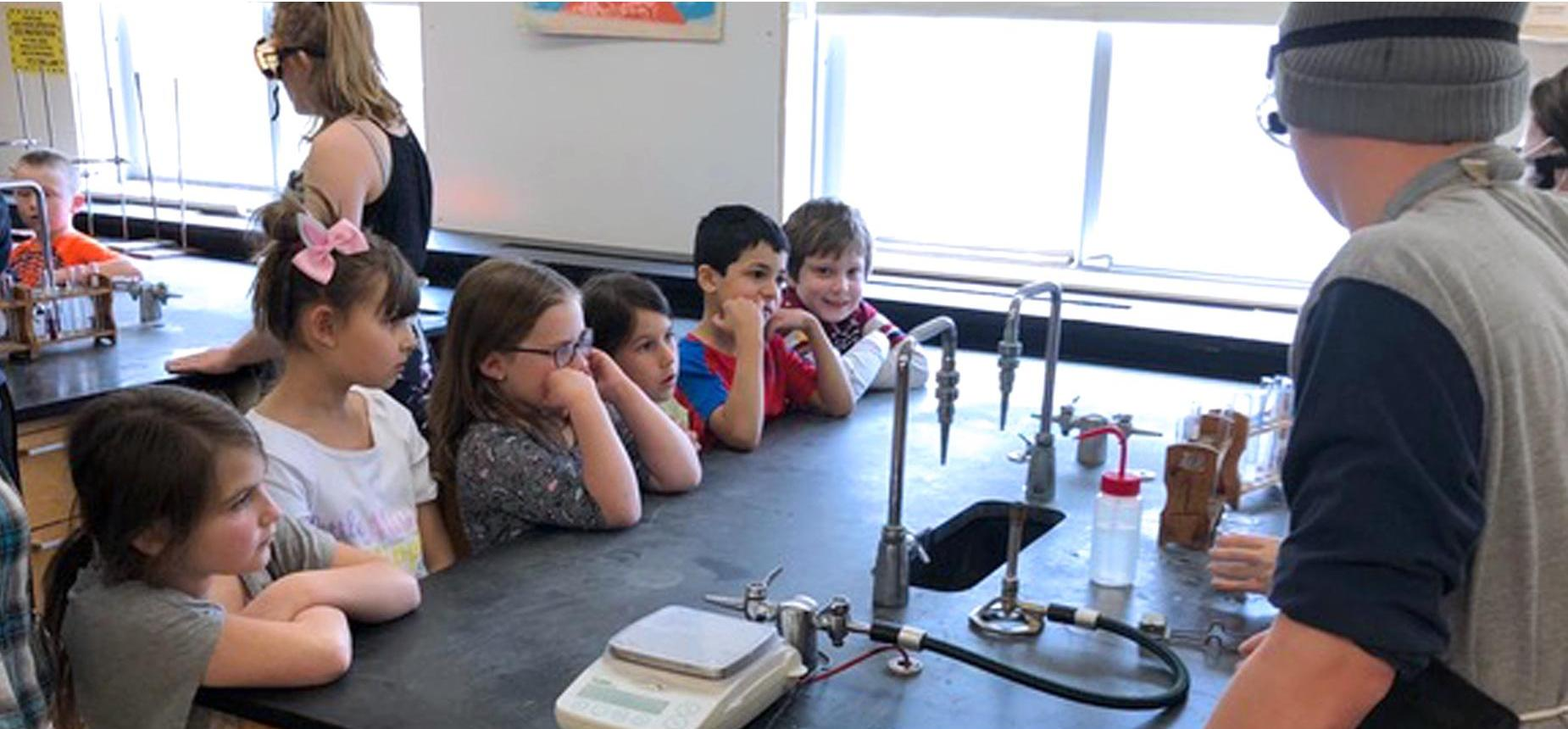 Elementary students watching a chemistry experiment in the high school science room