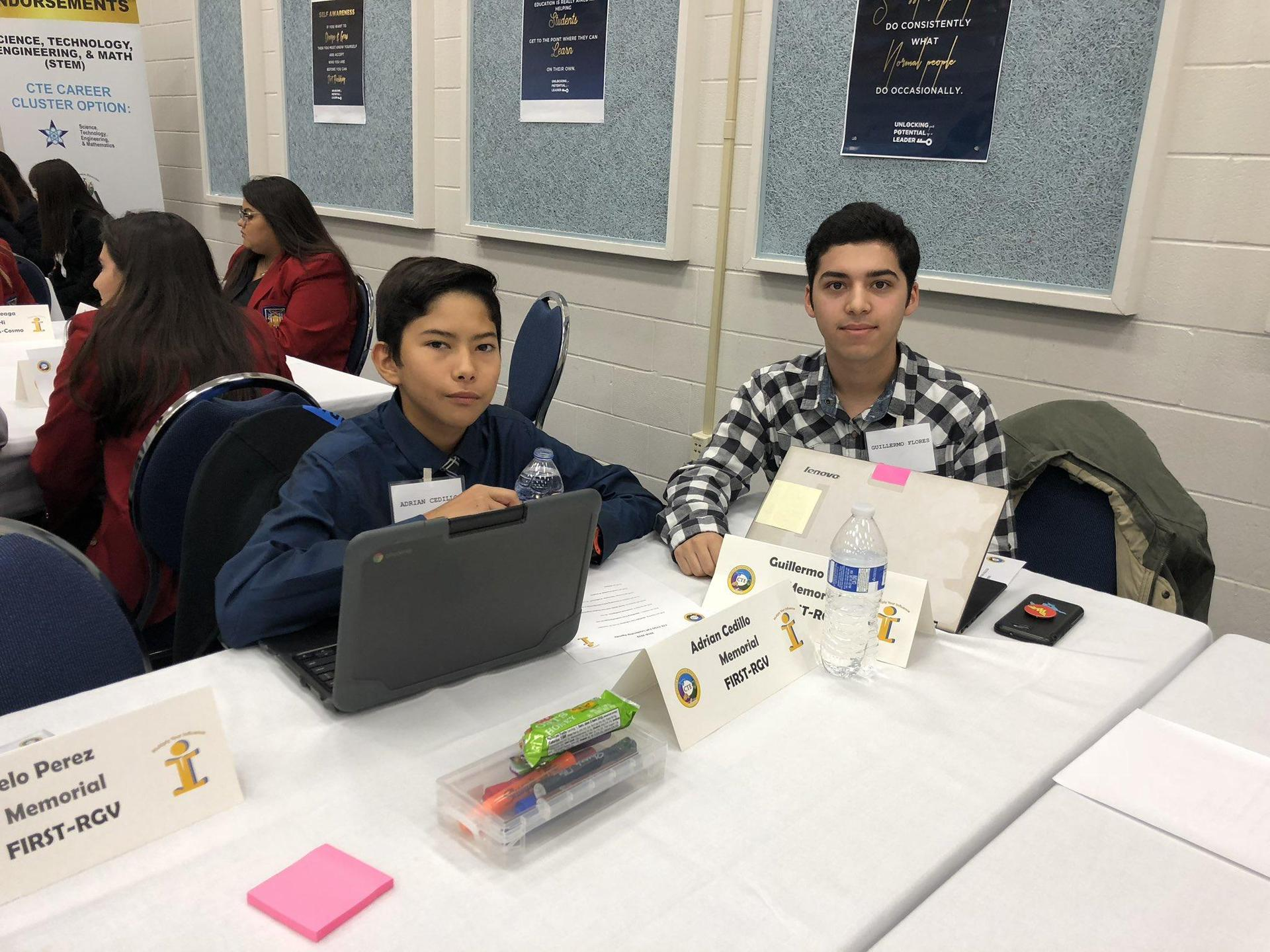 two students behind table in a competition event
