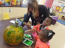 teacher helping a girl and boy decorate a pumpkin