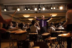 A photo of Mr. Pontiere conducting the OLSH band from the perspective of the band students.