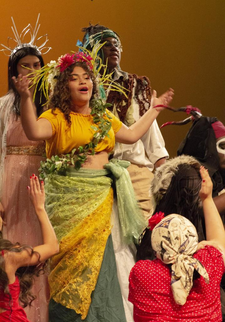 A scene with several cast members, with Asaka, the Mother of Earth, played by Daicia Eugene, at the center