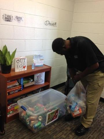 GOA recycles. Mr. White placing soda cans in designated bin.