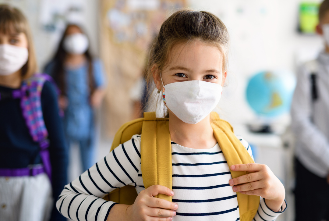 girl with mask and backpack at school
