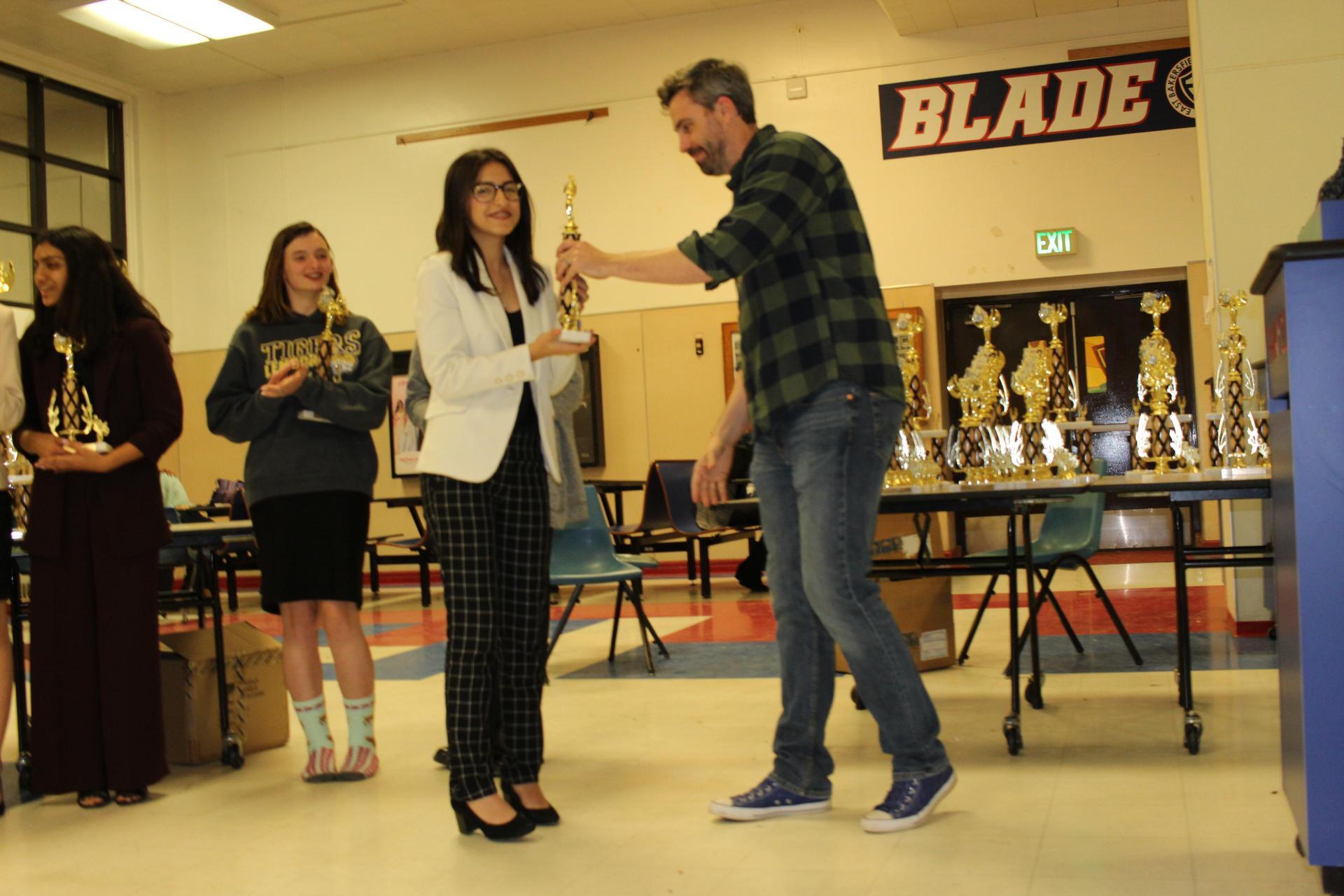 Daneli Santillan receiving a trophy