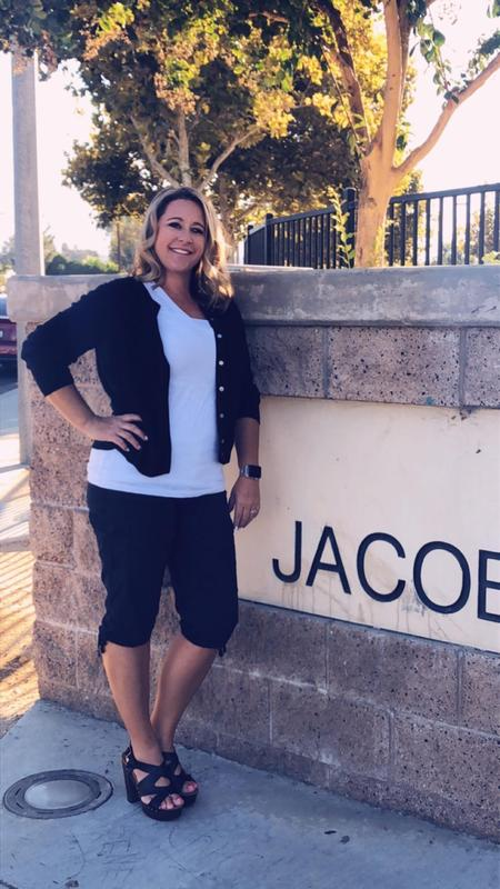 Melissa Mercer standing in front of a Jacob Wiens sign.