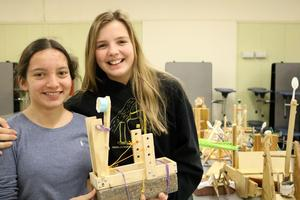 Edison 8th graders Anna Bongiovanni (left) and Katherine Gibbemeyer hold a catapult they designed and tested as part of a Science Olympiad on Jan. 28 that brought 8th graders from both intermediate schools together at Roosevelt for a series of design challenges, explorations, and experiments.