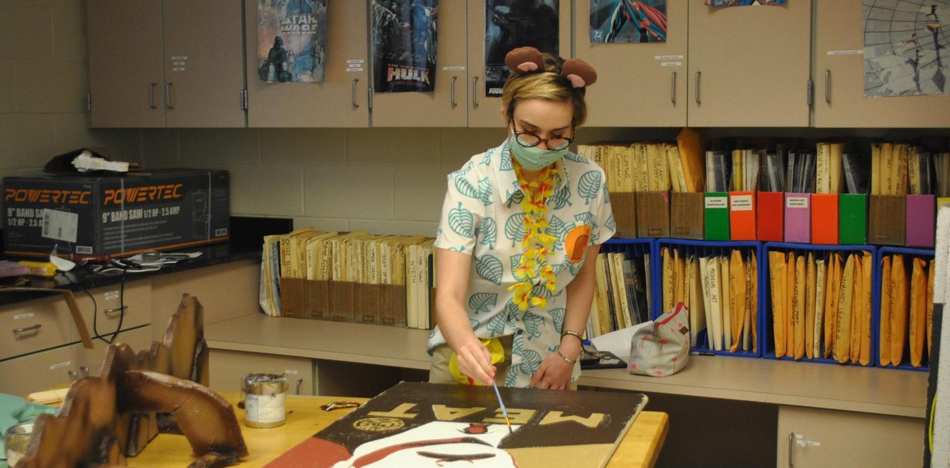 student in costume doing artwork.