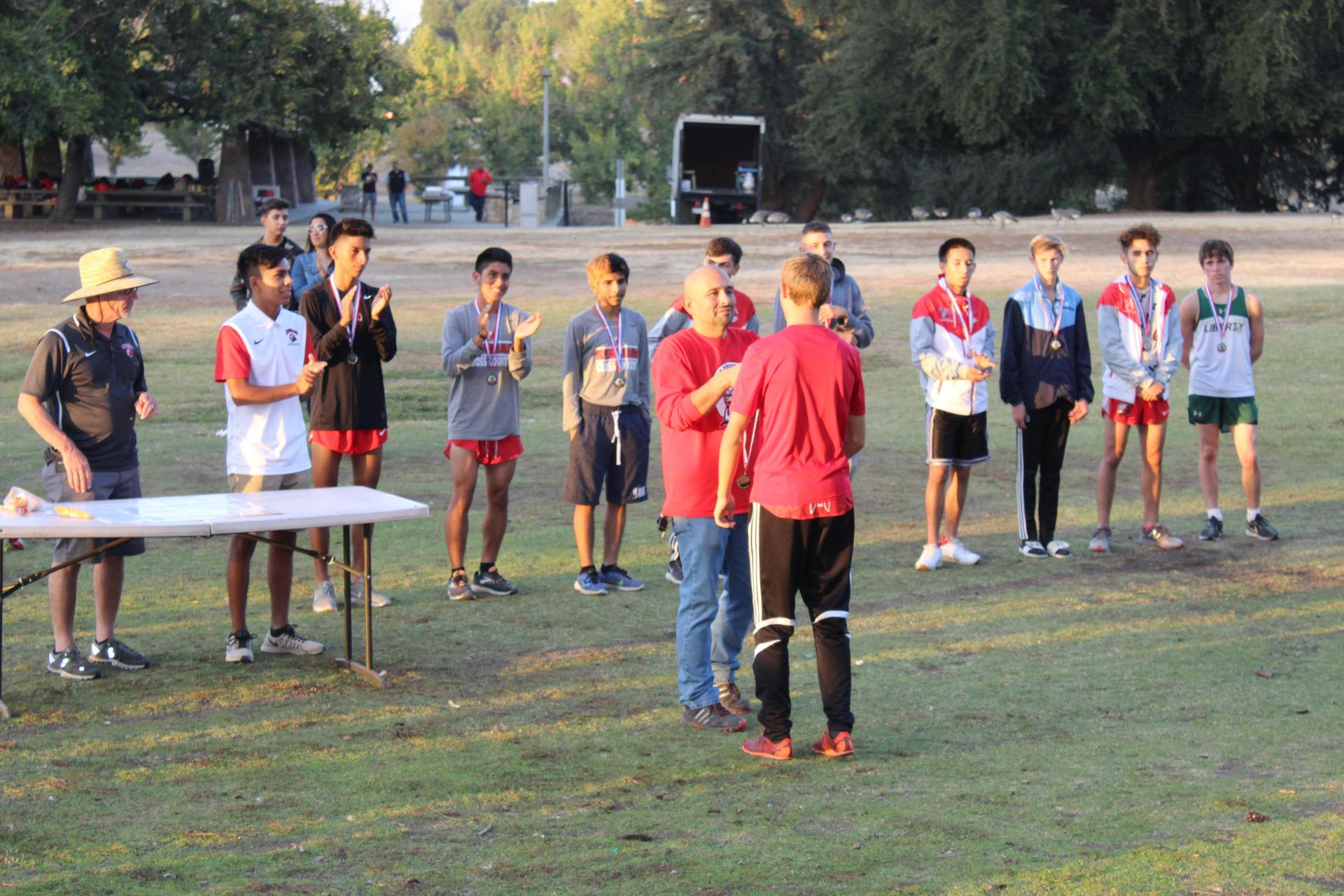Varsity Boys First Place Medal is awarded.