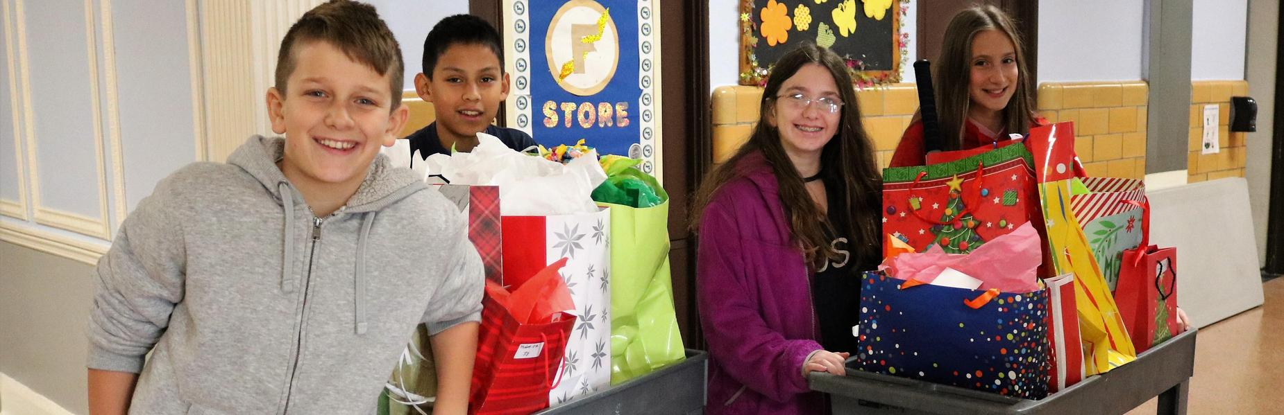 Franklin 5th graders pose with holiday gift donations to bring holiday cheer to others.