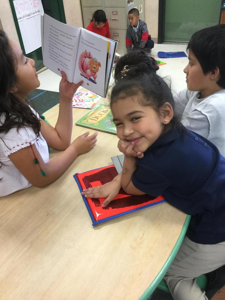 kindergarten student is read to by two third graders