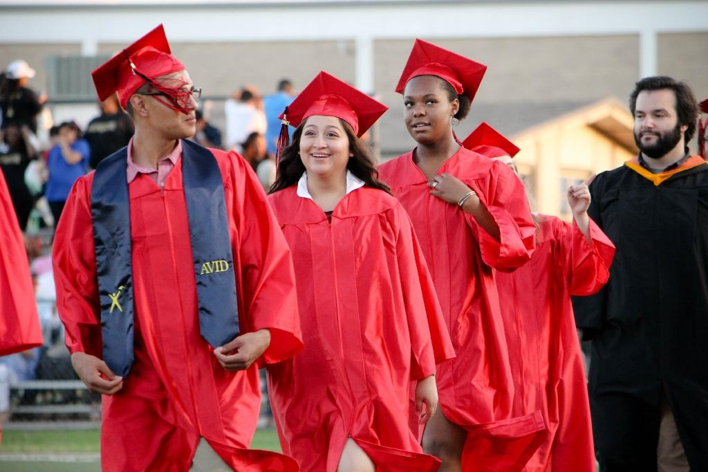 students of the victoria east high school 2018 graduating walking into memorial stadium, smiling students