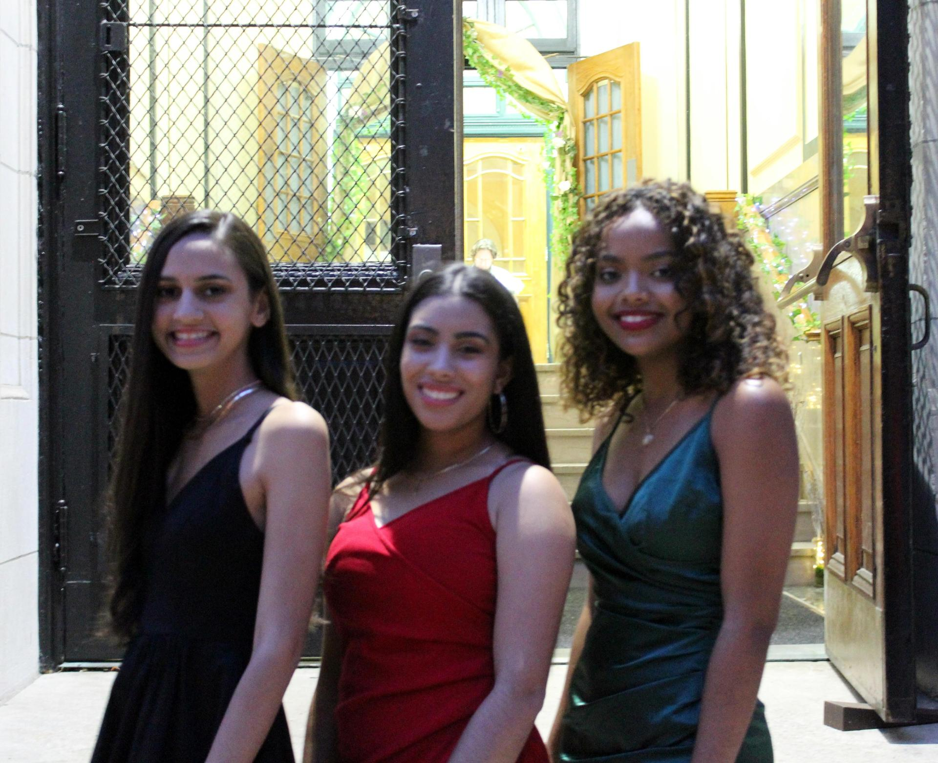 Three girls in formal wear by the front door of a school
