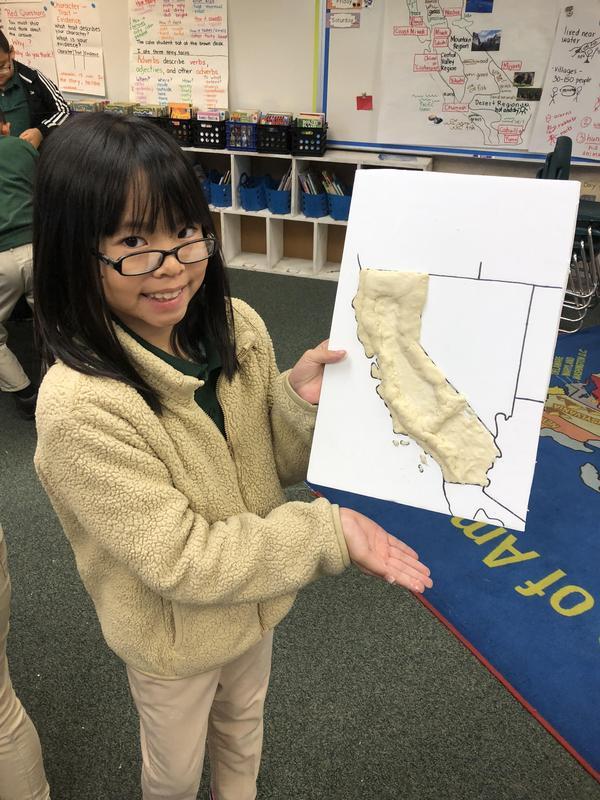 A student shows off her salt dough map