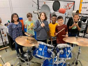 6 students pose at a drum set with drumsticks in their hands