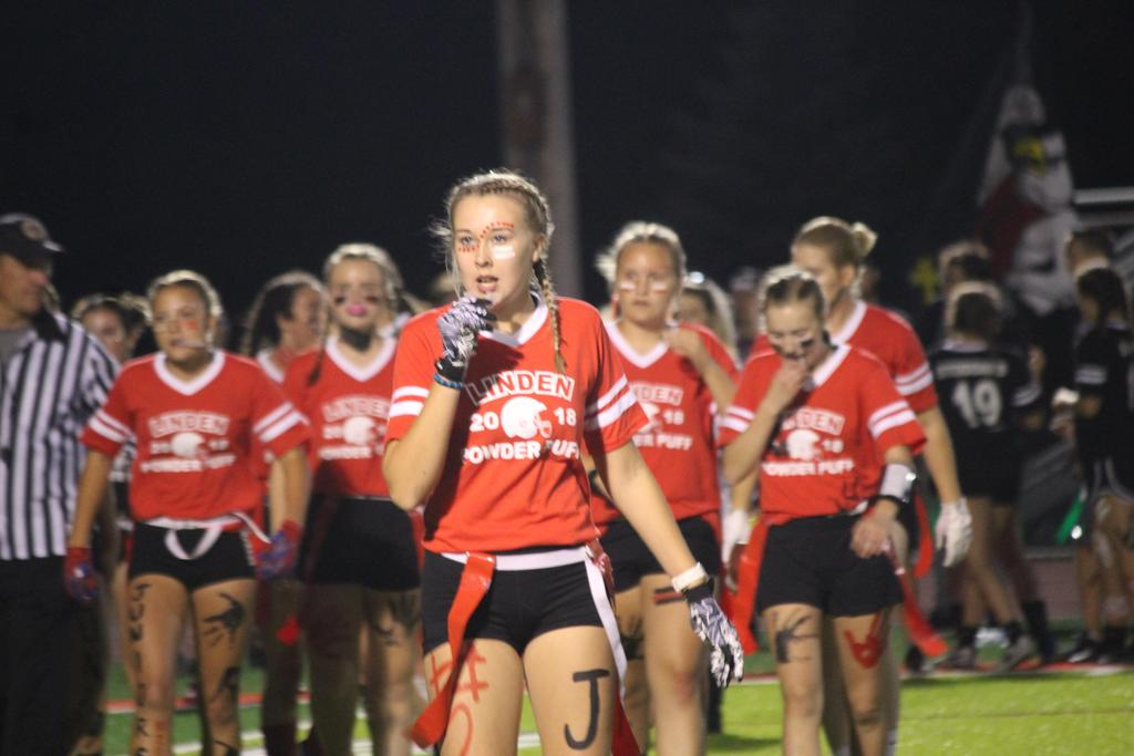 A powderpuff football player putting her mouth guard in