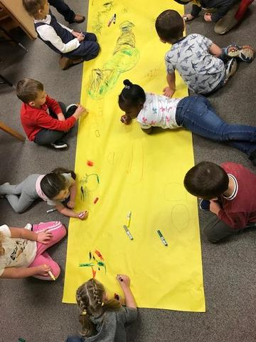 Syring - GSRP students engaged in creating a wall chart while coloring and labeling the chart on the floor.