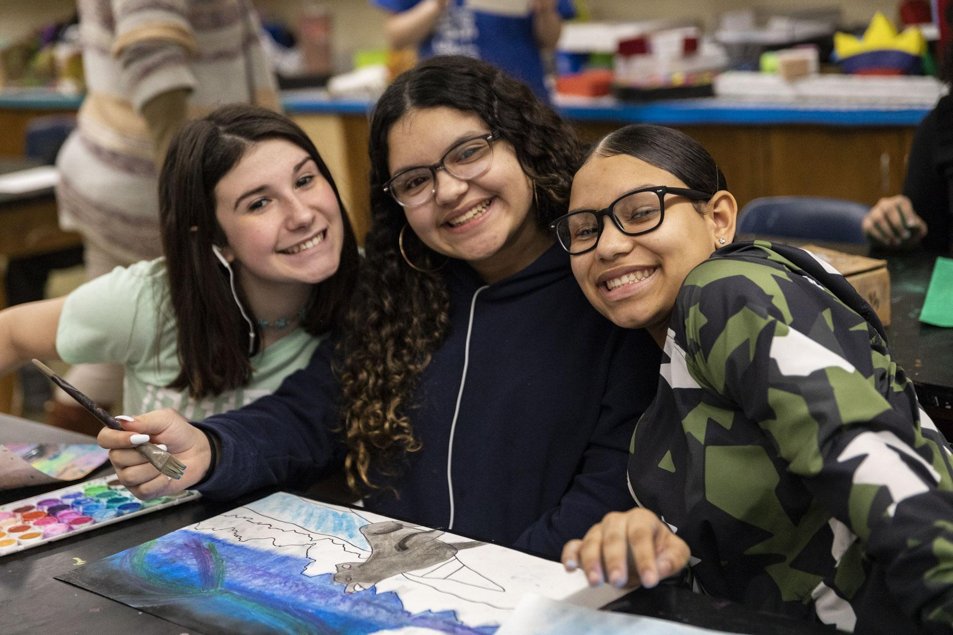 Three students smiling in art class