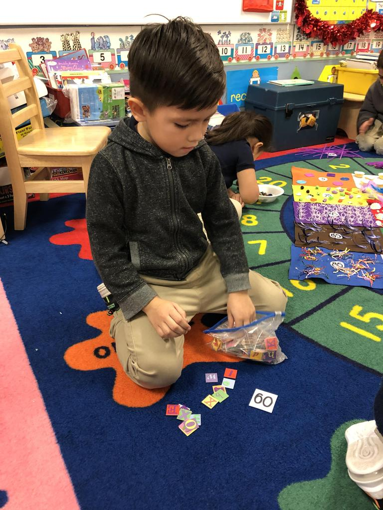 little boy sitting on the class rug taking tiles out of plastic bag