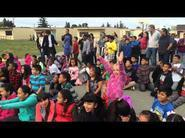Picture of Elementary Students Sitting in Large Group on Grass at a School