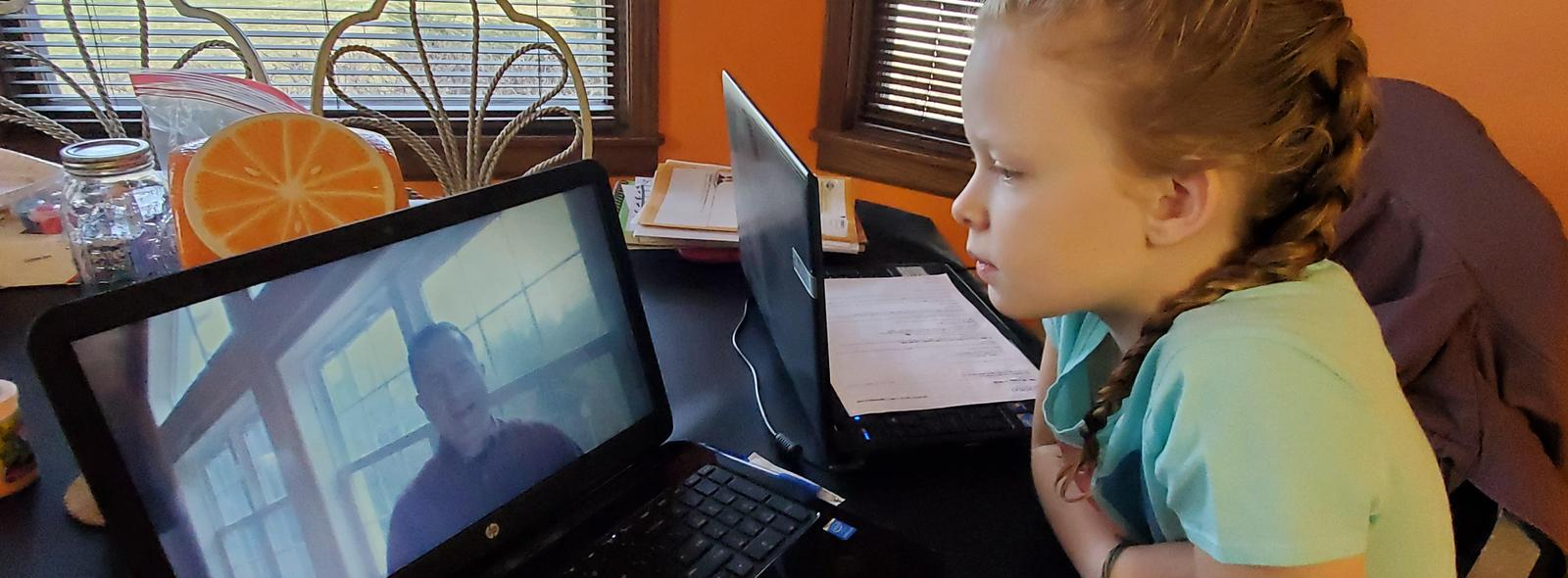 a girl watches mr. rollandini on the computer screen