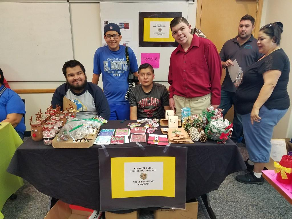 Students sitting and standing at table selling crafts