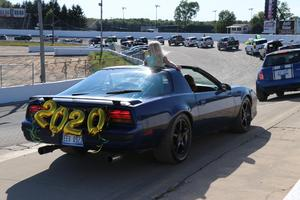 an alamo student waves from a convertible with balloons on the back as they go around the track