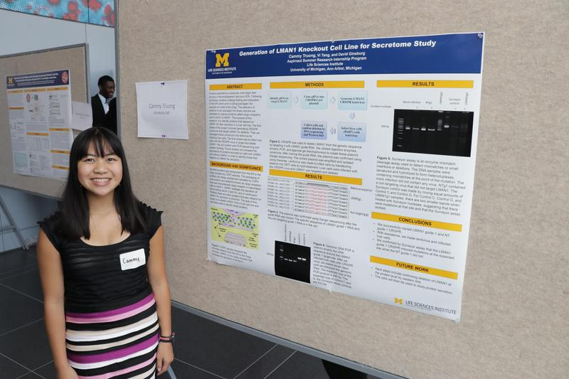 Cammy Truong stands by her research poster.