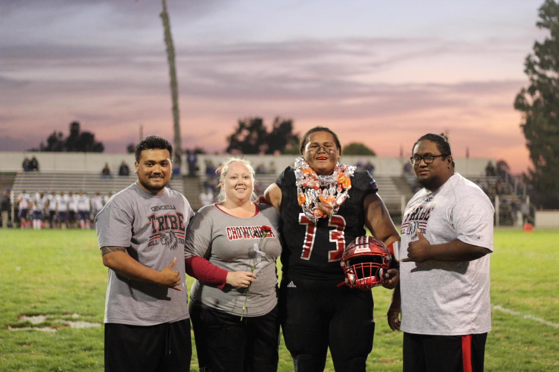 Senior football player Alfred Maui Laloata and his escorts.