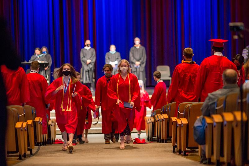 STUDENT IN RED GRAD GOWN WALKS UP AISLE