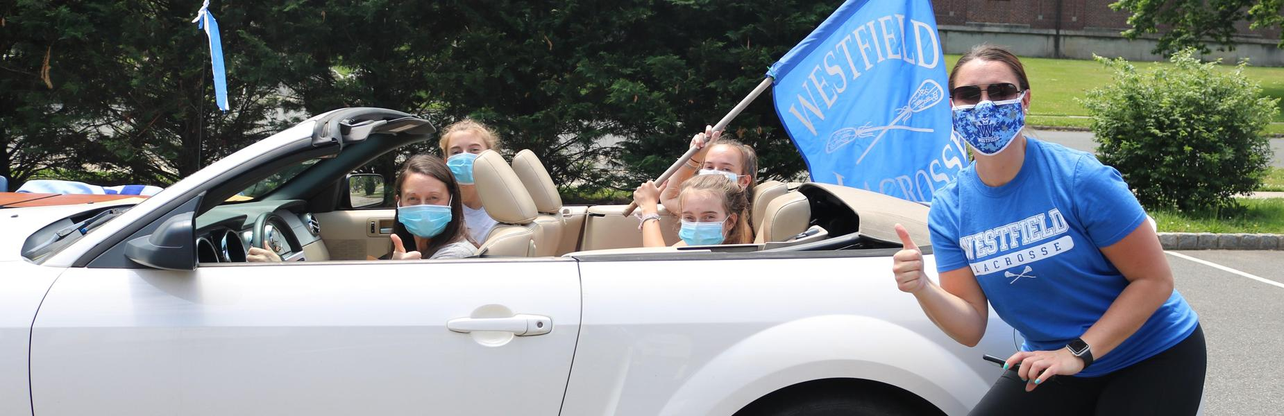 Photo of WHS lacrosse coach next to car with players picking up varsity letters during COVID-19 restrictions.