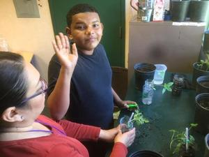 student and teacher next to plants in pots