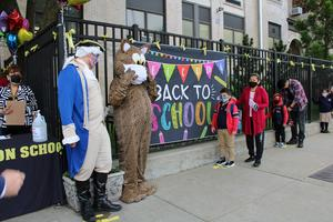Jefferson impersonator and jaguar mascot standing at front of line of students