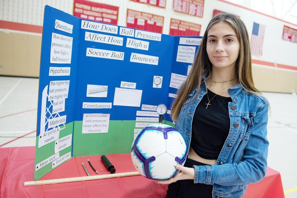 A female student holds a soccer ball and stands in front of her project