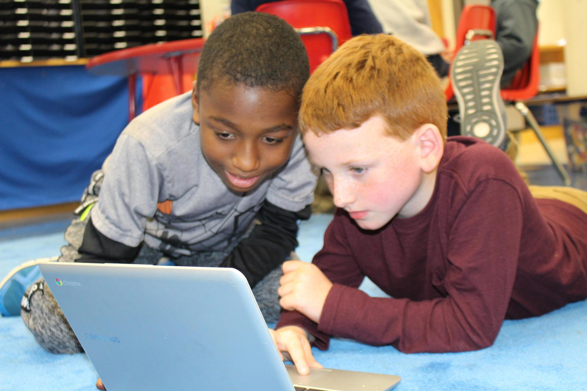 students collaborating with a chrome book