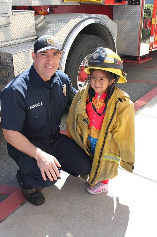 Firefighter & child from babysitting trying on hat and coat