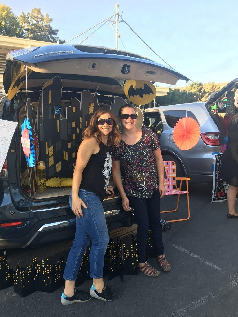 two adults in front of Bat Man themed trunk