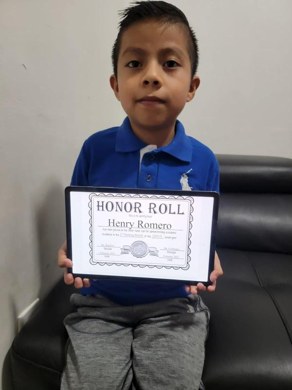 Henry holding honor roll certificate